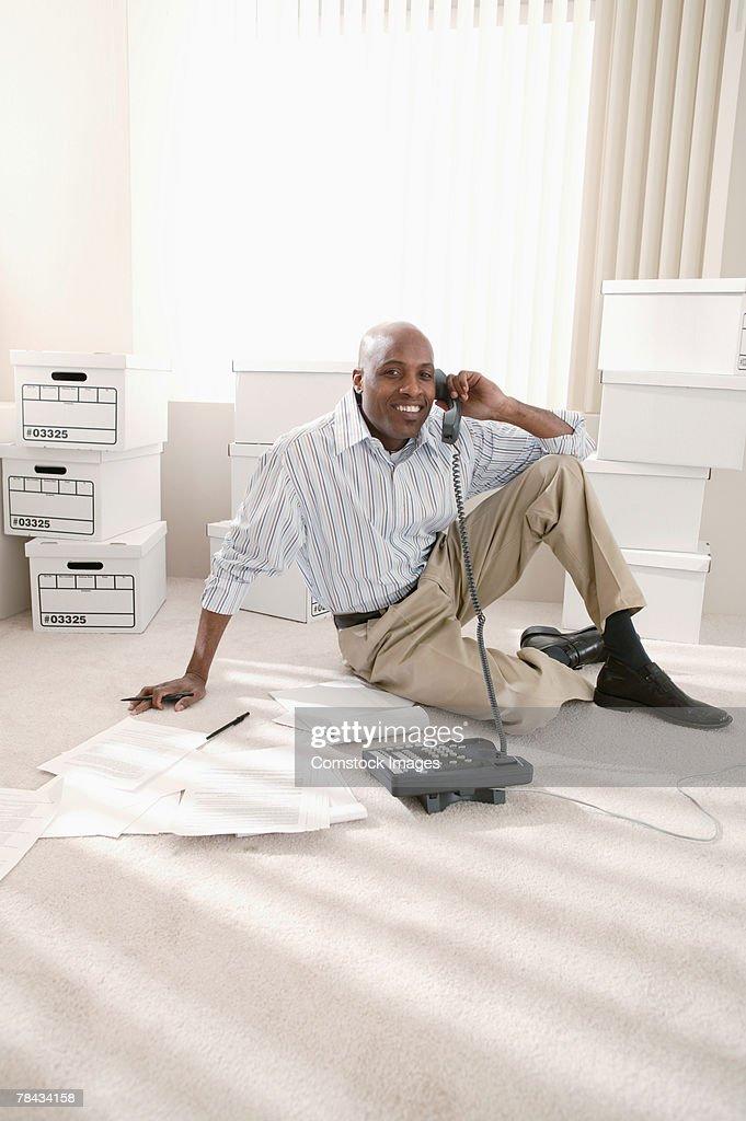 Businessman sitting on floor of office on telephone : Stockfoto