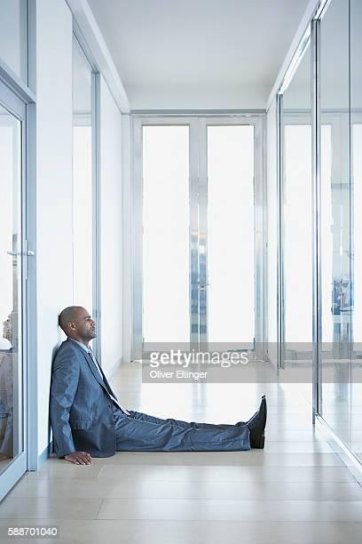 businessman sitting on floor - oliver eltinger stock-fotos und bilder