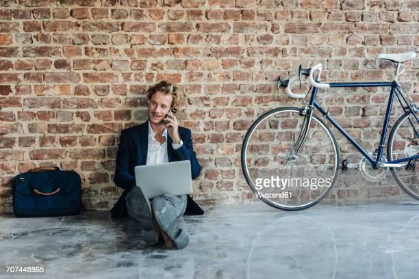 businessman sitting on floor using laptop and cell phone - freischaffender stock-fotos und bilder