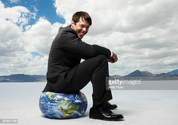 Businessman Sitting on Globe, Laughing