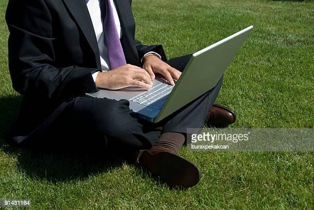 Businessman sitting on grass using laptop, Istanbul, Turkey