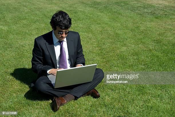 Businessman sitting on grass using laptop, Zekeriyaköy, Istanbul, Turkey
