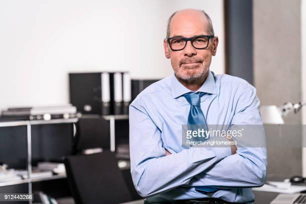 ein geschäftsmann sitzt auf dem tisch und schaut in die kamera - repicturing homeless stock-fotos und bilder
