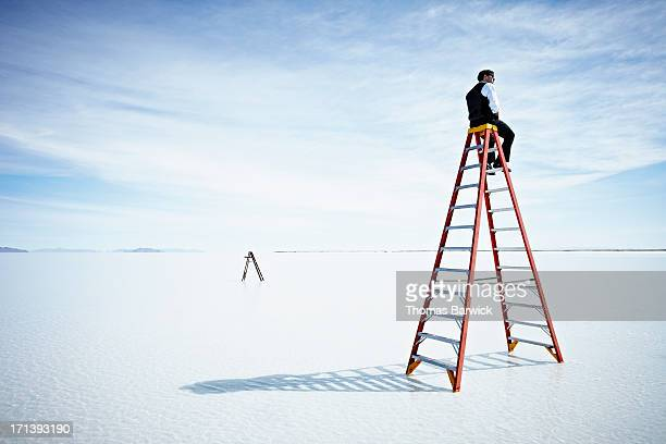 Businessman sitting on large ladder in lake