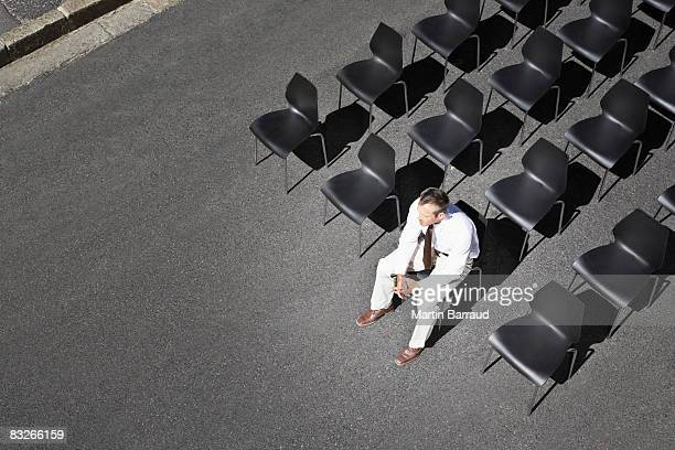 businessman sitting on office chair in roadway - imbalance stock photos and pictures