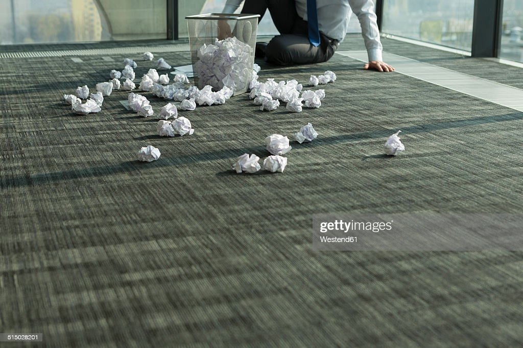Businessman sitting on office floor surrounded by crumpled paper : Stock Photo