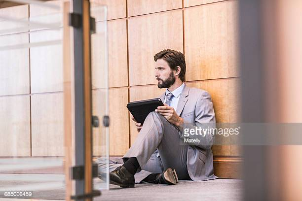 Businessman sitting on office floor using digital tablet