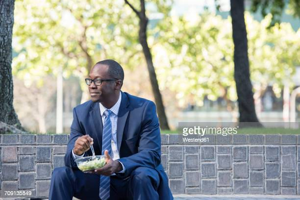 businessman sitting on outdoor stairs having lunch - lunch break stock photos and pictures
