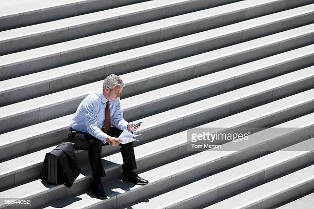 Geschäftsmann, sitzen auf outdoor Stufen und SMS