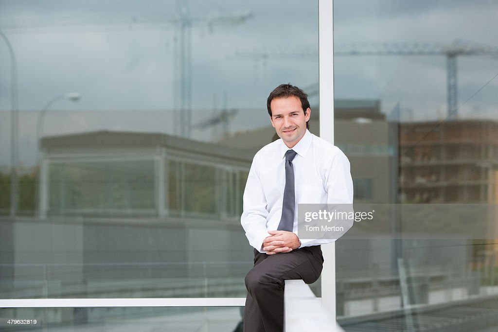 Businessman sitting on railing : Stock Photo