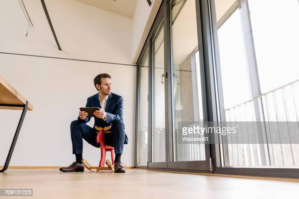 Businessman sitting on rocking horse with tablet