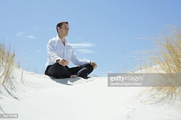 Businessman sitting on sand dune, meditating
