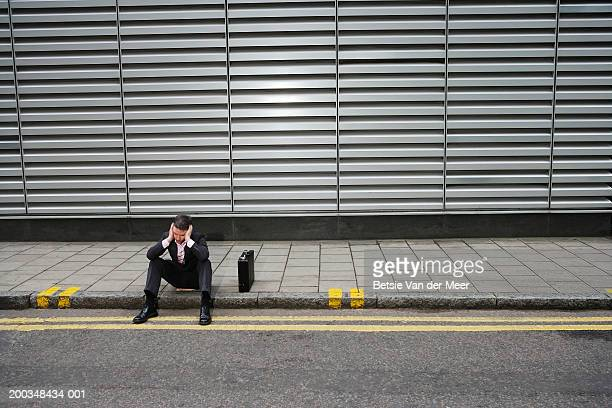 businessman sitting on side of road by briefcase - curb stock pictures, royalty-free photos & images
