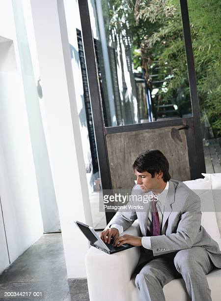 Businessman sitting on sofa, using laptop