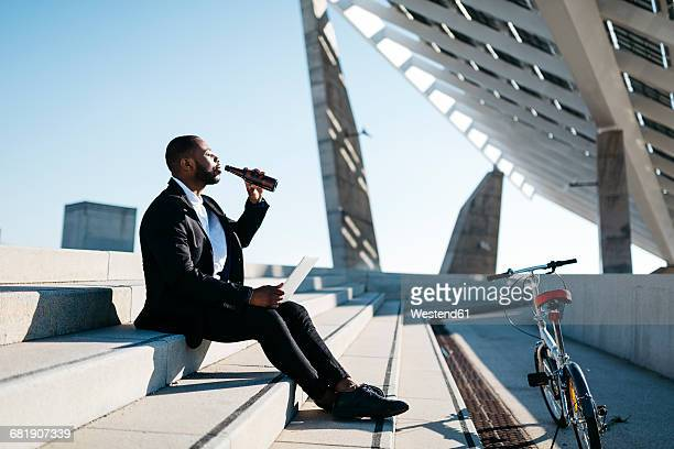 Businessman sitting on stairs drinking beer from bottle