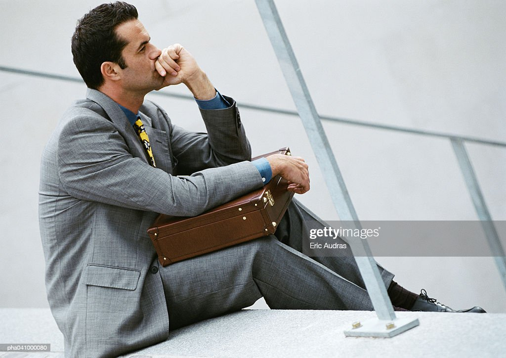 Businessman sitting on stairs, holding briefcase : Foto stock