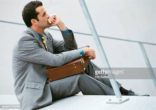 Businessman sitting on stairs, holding briefcase