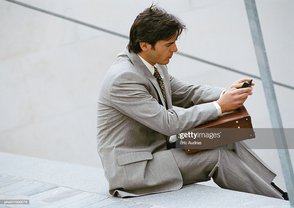 Businessman sitting on stairs, looking at cell phone : Stockfoto
