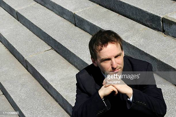 Businessman sitting on stairs.