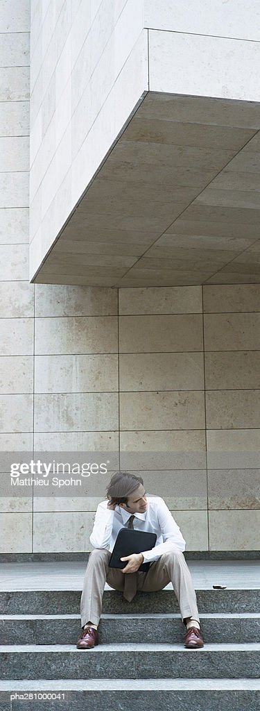 Businessman sitting on steps, holding file : Stock Photo
