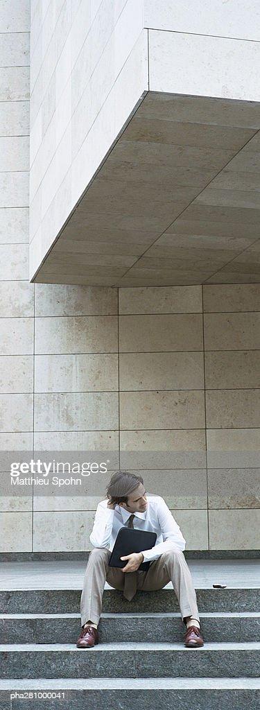 Businessman sitting on steps, holding file : Stock-Foto