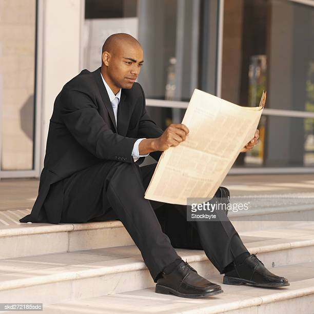 Businessman sitting on steps reading a newspaper
