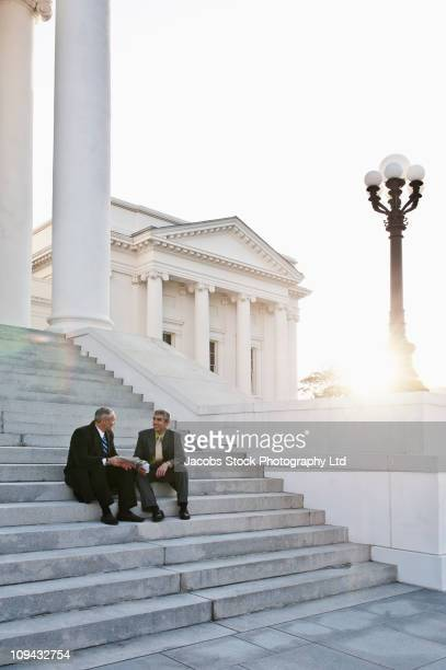Businessman sitting on steps talking