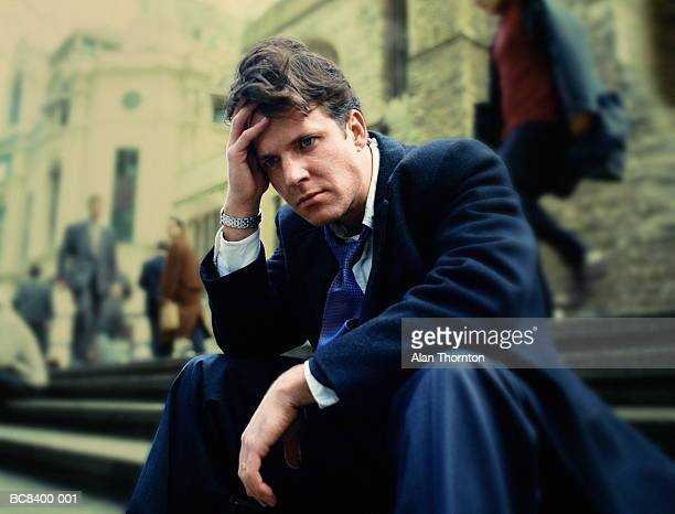 Businessman sitting on steps, with pensive expression (Enhancement)