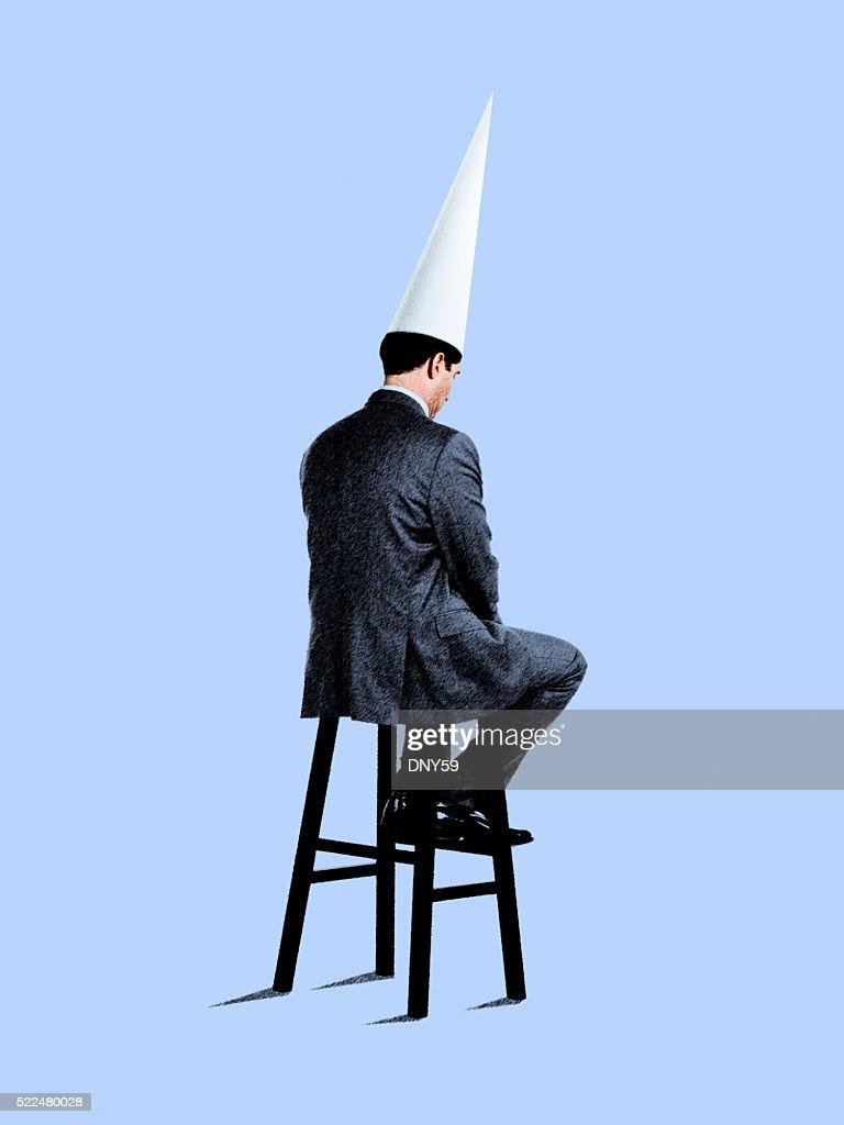 Businessman Sitting On Stool Wearing Dunce Cap : Stock Photo