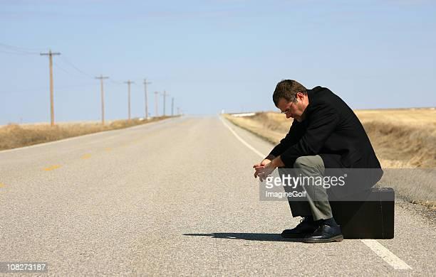 empresário sentado na mala em estrada - homens de idade mediana imagens e fotografias de stock