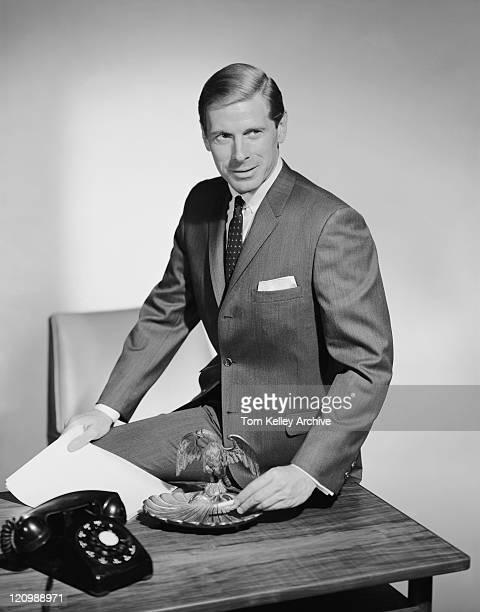 Businessman sitting on table near ash tray