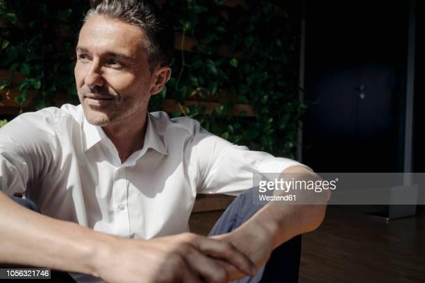 businessman sitting on the floor in green office - oberhemd stock-fotos und bilder