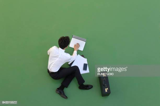 Businessman sitting on the floor using his laptop