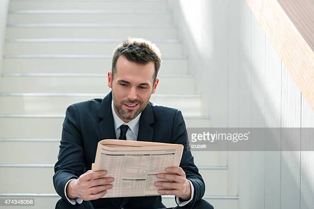 Homme d'affaires assis sur l'escalier intérieur et de lecture de journal