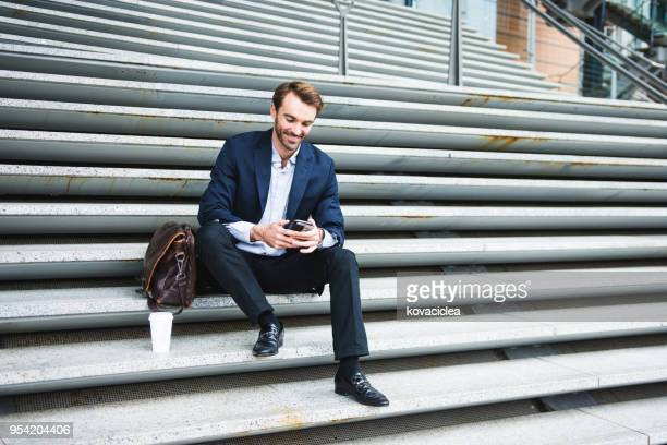 businessman sitting on the stairs with his suitcase and smart phone - smart casual stock pictures, royalty-free photos & images