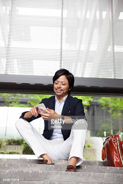 Businessman sitting on the steps working on phone