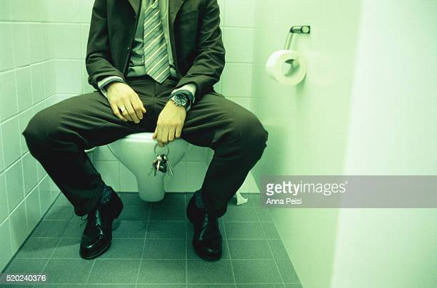 Businessman sitting on toilet