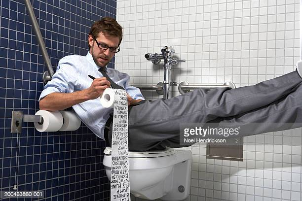 Businessman sitting on toilet with feet up, writing list on paper