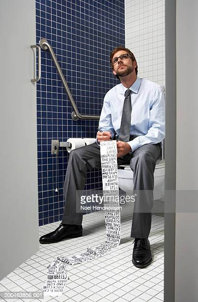 Businessman sitting on toilet writing list on paper