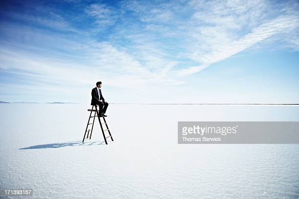 Businessman sitting on top of ladder in lake