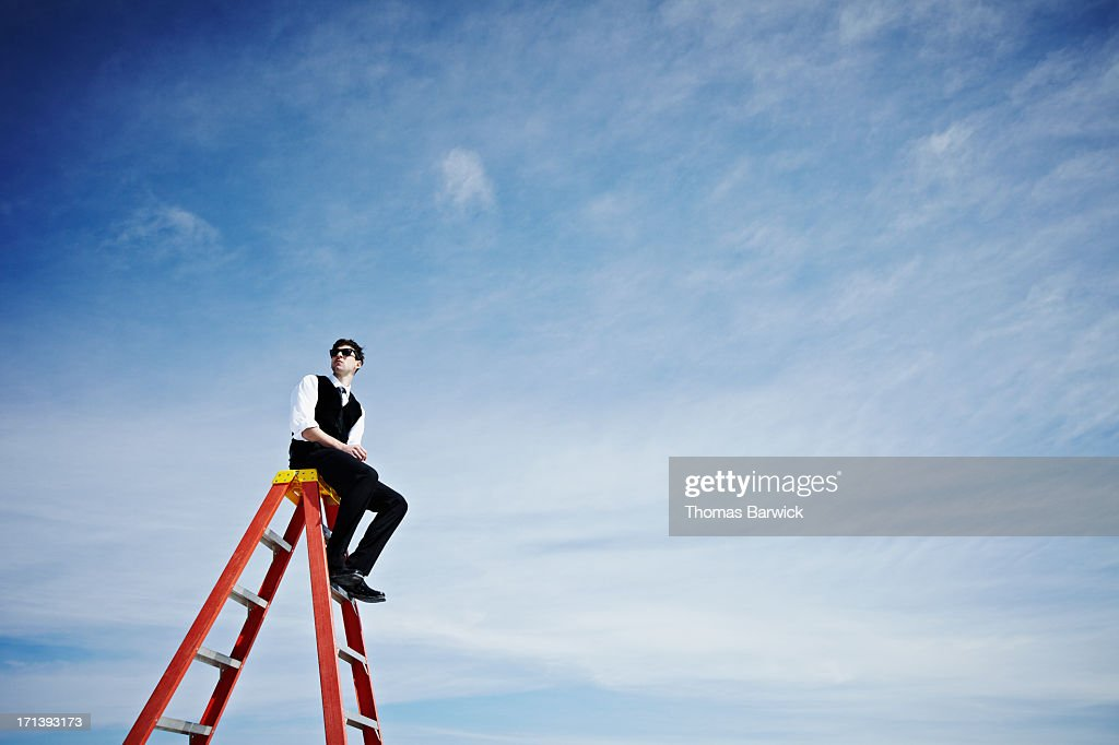 Businessman sitting on top of ladder looking out : Stock Photo
