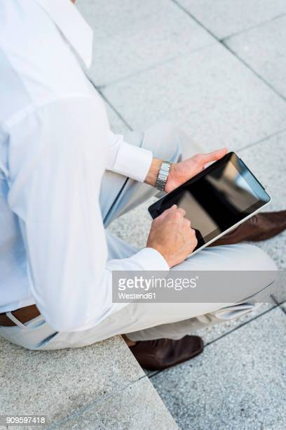 Businessman sitting on wall using tablet, partial view