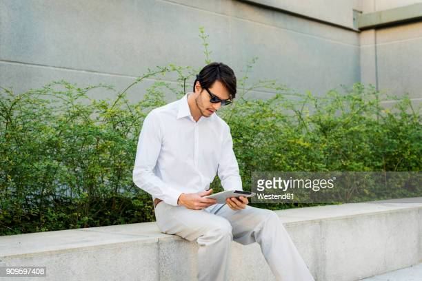 Businessman sitting on wall using tablet
