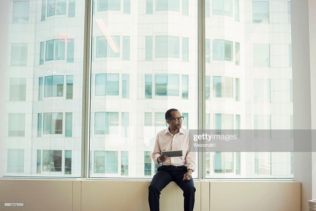 Businessman sitting on window sill holding digital tablet : Stock Photo