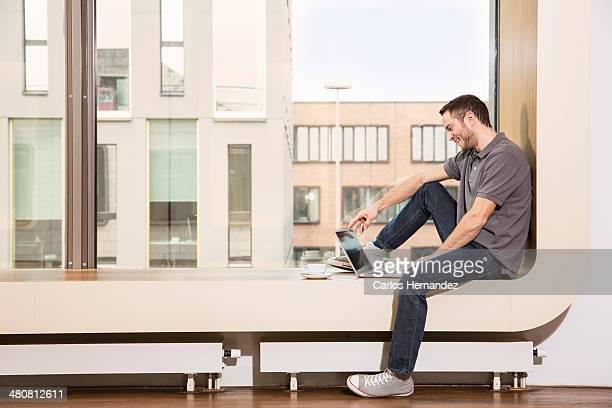 businessman sitting on windowsill using laptop - rebord de fenêtre photos et images de collection