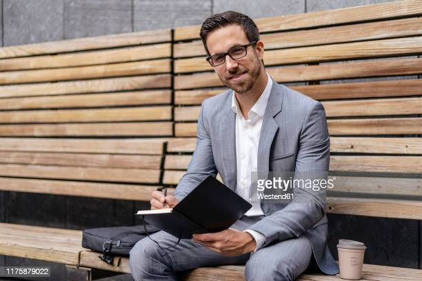 businessman sitting on wooden bench in the city writing into notebook - mid adult men stock pictures, royalty-free photos & images