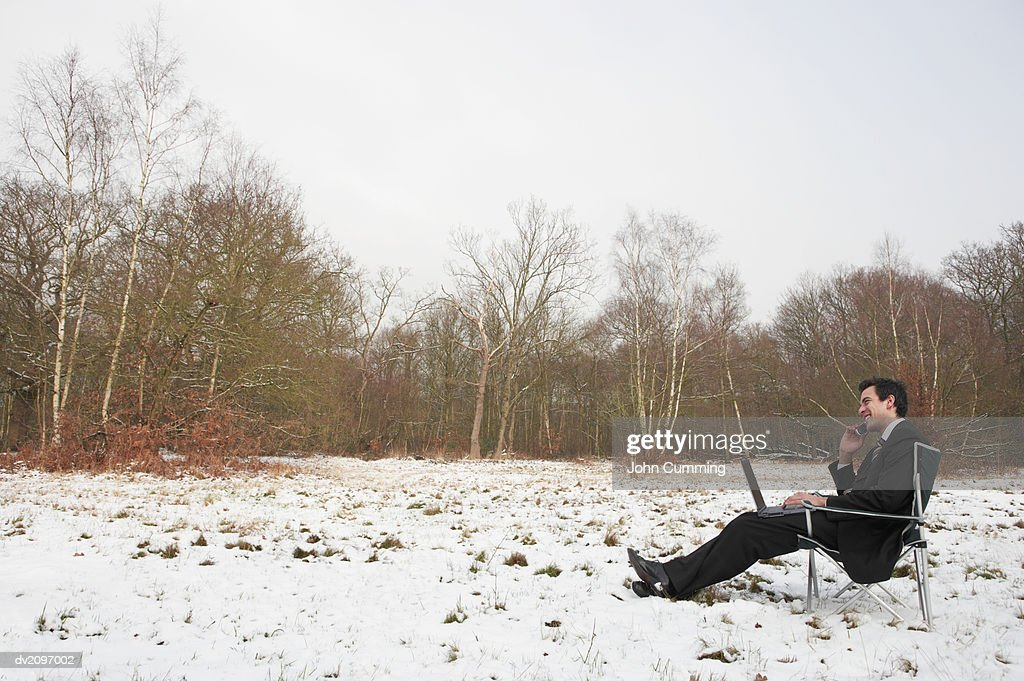 Businessman Sitting Outdoors in Snow Using a Laptop Computer : Stock Photo