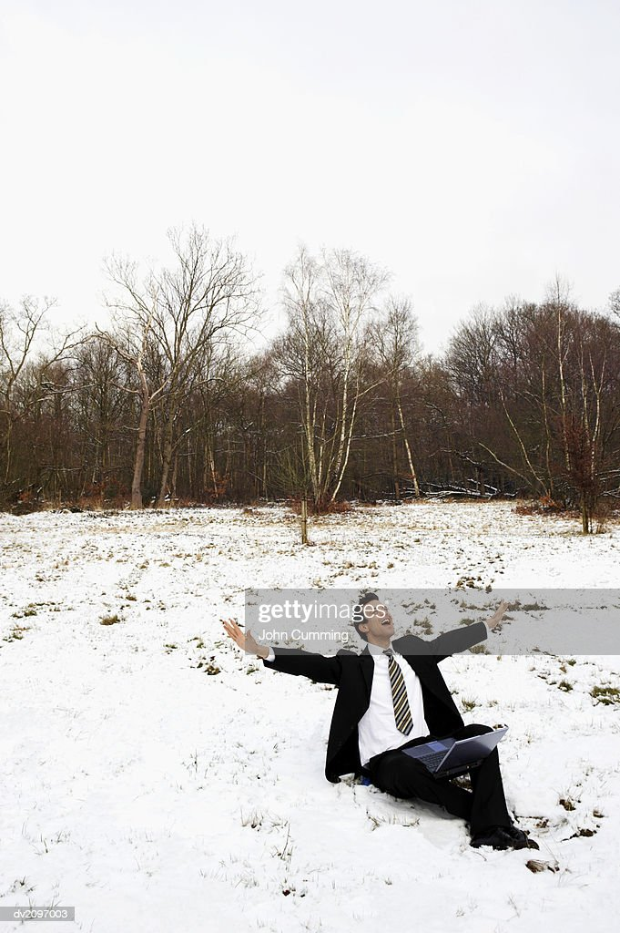 Businessman Sitting Outdoors in Snow With a Laptop Computer and His Arms Out : Stock Photo