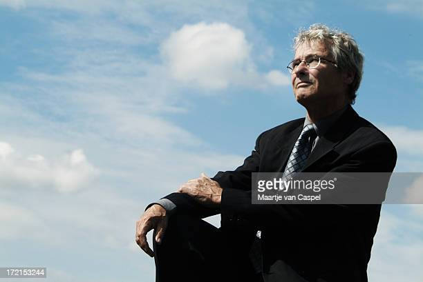 Businessman sitting outside looking up in the sky