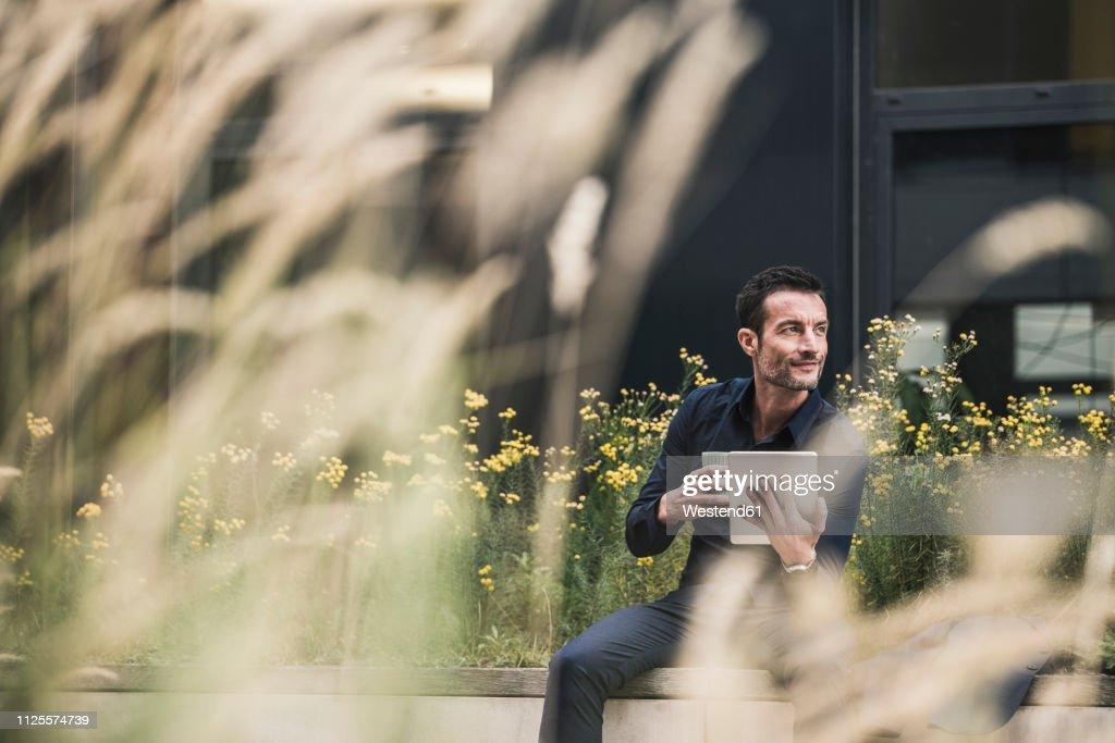 Businessman sitting outside, taking a break, drinking coffee, using digital tablet : ストックフォト